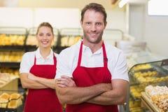 Portrait du sourire deux boulangers avec des bras croisés Photos libres de droits