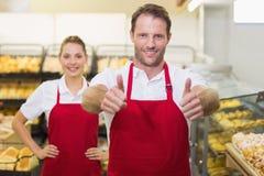 Portrait du sourire deux boulangers avec le pouce  Images stock