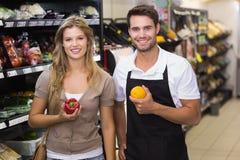 Portrait du sourire femme assez blonde achetant un légume au vendeur image libre de droits