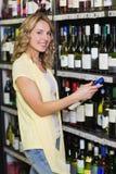 Portrait du sourire femme assez blonde regardant la bouteille de vin Images stock