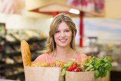 Portrait du sourire produits alimentaires de achat de femme assez blonde Images stock