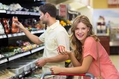 Portrait du sourire produits alimentaires de achat de femme assez blonde Photos libres de droits