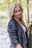 Portrait du sourire womanleaning contre un tronc d'arbre Photo libre de droits