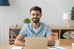 Portrait du travailleur de sexe masculin heureux s'asseyant à la table utilisant l'ordinateur portable photo libre de droits