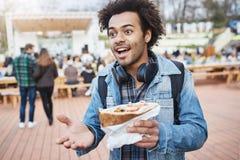 Portrait du type à la peau foncée attirant avec les cheveux Afro faisant des gestes tout en discutant quelque chose avec des amis Image stock