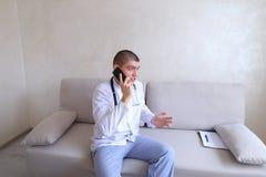 Portrait du type de docteur qui sur le mobile donne des conseils aux patients SI Photographie stock libre de droits