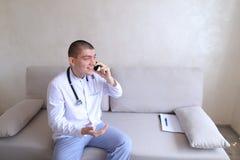 Portrait du type de docteur qui sur le mobile donne des conseils aux patients SI Image stock