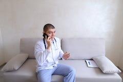 Portrait du type de docteur qui sur le mobile donne des conseils aux patients SI Photographie stock