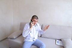 Portrait du type de docteur qui sur le mobile donne des conseils aux patients SI Photo stock