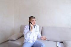 Portrait du type de docteur qui sur le mobile donne des conseils aux patients SI Images stock