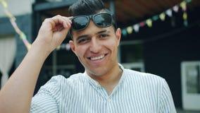Portrait du type gai de métis soulevant des lunettes de soleil dehors le jour d'été banque de vidéos