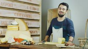Portrait du vendeur amical dans le fromage de magasin Il regarde dans l'appareil-photo : sourire banque de vidéos