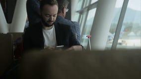 Portrait du voyageur masculin qui écrit un email sur son smartphone dans l'aéroport clips vidéos