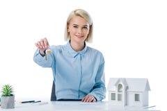 portrait du vrai agent immobilier de sourire montrant des clés sur le lieu de travail avec le modèle de maison Photographie stock libre de droits