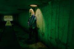 Portrait Dystopian de modèle posant en rivière des eaux d'égout dans le tunnel sous la ville Lit avec le feu vert Image libre de droits