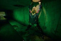 Portrait Dystopian de modèle posant en rivière des eaux d'égout dans le tunnel sous la ville Lit avec le feu vert Images libres de droits