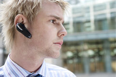 Portrait with Earphone. Young businessman using a hands free device to speak on the phone, in the financial district Royalty Free Stock Photo