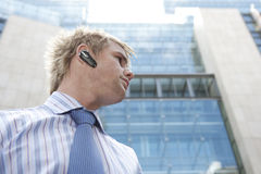 Portrait with Earphone. Young businessman using a hands free device to speak on the phone, in the financial district Stock Images