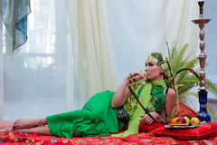 Portrait of east woman. Portrait of beautiful east tsarina, on a carpet with a hookah and fruit Stock Photos