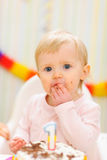 Portrait of eat smeared baby eating birthday cake Stock Photo