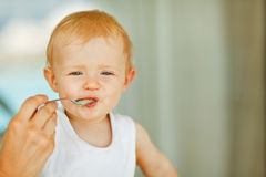 Portrait of eat smeared baby feeding by mom Royalty Free Stock Photos