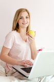 Portrait of eating apple beautiful gentle sweet young woman in bed with laptop pc computer looking at camera Royalty Free Stock Image