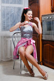 Portrait of eating tasty cake glamour beautiful young woman pin-up girl having fun sitting in kitchen in sexy dress. Picture of glamour beautiful young sensual Stock Photo