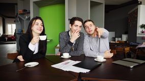 Portrait of educated students of guys and girls who communicate. Two guys and beautiful girl, students or classmates communicate and laugh, sitting at table and Stock Photography