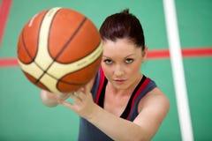 Portrait einer athletischen Frau, die Basketball spielt Lizenzfreie Stockfotos