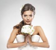 Portrait einer Braut, die einen Blumenstrauß der Rosen anhält Lizenzfreies Stockbild