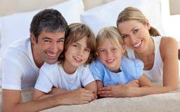 Portrait einer fröhlichen Familie, die in einem Bett liegt Stockbild