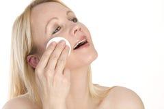 Portrait einer Frauenreinigung ihr Gesicht. Stockfotografie
