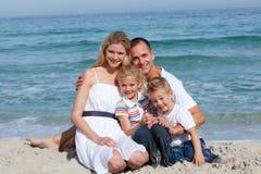Portrait einer freundlichen Familie, die auf dem Sand sitzt Lizenzfreies Stockbild