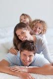 Portrait einer frohen Familie, die auf einander liegt Lizenzfreie Stockfotografie