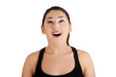 Portrait einer glücklichen überraschten jungen Frau, die oben schaut. Stockfotografie