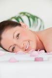 Portrait einer jungen Frau, die auf einer Massagetabelle liegt Stockbild