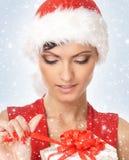 Portrait einer jungen Frau, die ein Geschenk öffnet Stockbild