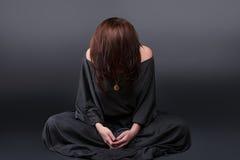 Portrait einer jungen kaukasischen betenden Frau Gebetsmädchen kleidete in den Kleidungen einer Nonne auf grauem Studiohintergrun Lizenzfreies Stockfoto