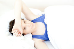 Portrait einer kranken jungen Frau, die auf ihrem Bett liegt Stockfoto
