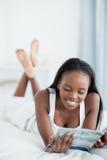 Portrait einer lächelnden Frau, die eine Zeitschrift liest Lizenzfreie Stockfotos