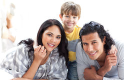 Portrait einer liebevollen Familie, die auf dem Fußboden liegt stockbilder