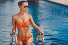 Portrait einer schönen Frau durch das Pool Stockfotos