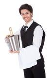 Portrait eines Butlers mit Flasche Champagner Stockfotografie