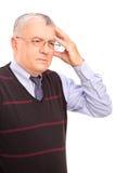 Portrait eines fälligen Mannes, der seinen Kopf anhält Stockbilder