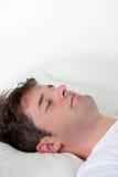 Portrait eines kaukasischen Mannes, der auf seinem Bett schläft Lizenzfreie Stockbilder