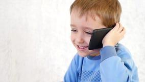 Portrait eines kleinen Jungen Das Kind nennt am Telefon und erfährt Gefühle der Freude und des Gelächters stock video