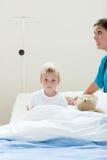 Portrait eines kranken kleinen Jungen auf einem Krankenhausbett Stockbild