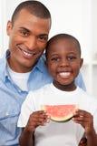 Portrait eines lächelnden Jungen, der Frucht isst Stockfoto