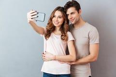 Portrait eines lächelnden jungen Paarumarmens Stockfotos