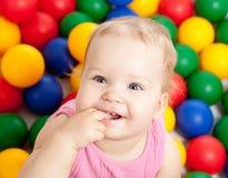 Portrait eines lächelnden Kindes unter bunten Kugeln Lizenzfreies Stockfoto